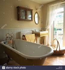 French Bathroom Sink Patterned Wallpaper And Roll Top Bath In Traditional Bathroom With
