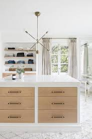 well appointed contemporary closet features a marble top white island finished with stained wood drawer fronts with gray pulls illuminated by a brass and