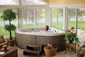 this naturally lit sunroom is home to a corner hot tub installing an indoor hot tub provides increased privacy