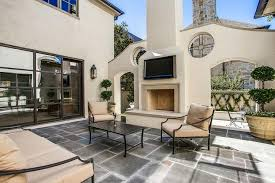 stucco outdoor fireplace and hearth with flat panel tv niche