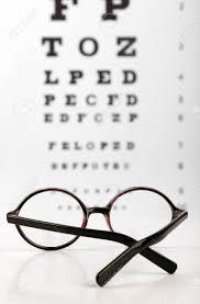 Glasses On Eye Chart Background Close Up