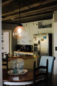 a large pendant lighting above a dining furniture black wood dining chairs and a soft blue allen roth