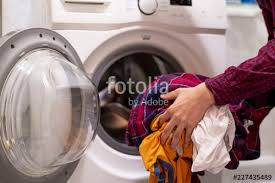close up hands loading dirty clothes into washing machine at home bathroom f