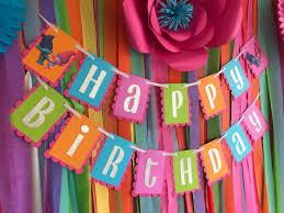 i love how makscraft layered this cute happy birthday banner over a wall of colorful crepe paper streamers for an eye catching and inexpensive party