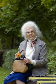Old Woman With Grey Hair And Glasses Sitting On The Bench In