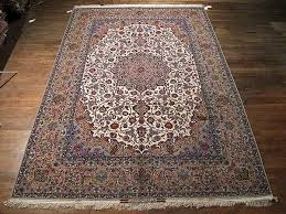 this persian rug of an ivory background includes an extensive variety of natural bright colors the main border is beige naturally matching the persian