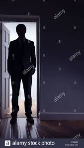 silhouette of a man standing in front of an open door stock image