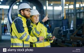 Portrait Of Male And Female Industrial Engineers In Hard Hats