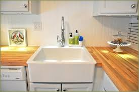 white utility sink cabinet for laundry with wooden countertop inspiring