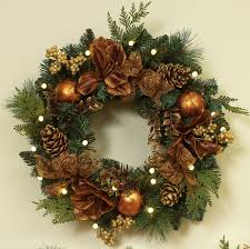 Interior. green Christmas Wreath with brown flowers and golden baubles also  golden pine cones.
