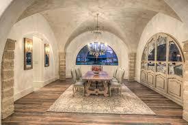 Mediterranean Dining Room with Chandelier, Hardwood floors, Custom  cabinetry, interior wallpaper, Columns
