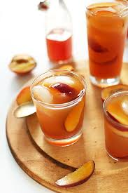 gles of sweet peach iced tea with ice cubes and slices of peaches in them