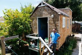 tiny houses prices. Aaron Castle Stands At The Back Porch Of His 139-square-foot Tiny Houses Prices