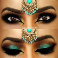 this eye makeup uses dark and teal eye shadow accentuated by heavy black liner and false eyelashes try this gorgeous exotic look today