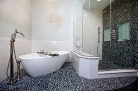 bathroom white oval freestanding acrylic bathtub next to black shower stall design on dark mosaic