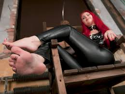 Redhead dominatrix and foot slaves