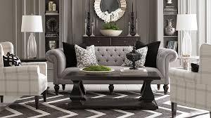 beautiful living room furniture of grey tufted fabric loveseat and white patterned wing back accent chairs front of black chest drawers under sculpture wall