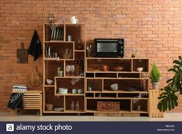 set of clean dishes with utensilicrowave oven on wooden shelves near brick wall