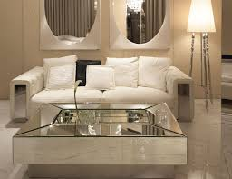 modern minimalist living room design with square glass top mirrored coffee table and white leather tufted sofa under pair of wall mounted oval mirror ideas