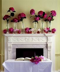 hot pink flowers decorating a fireplace mantle