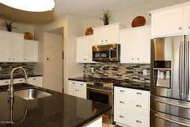 small u shaped modern kitchen with white cabinetry multi colored backsplash and stainless