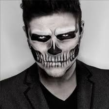 smartly dressed man wearing an angry skull face paint done with red and black