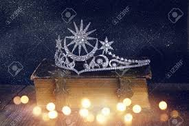 low key image of beautiful diamond queen crown on old book vine filtered with glitter