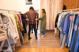 a beginner s guide to starting an online vintage shop racked a shopper and a sperson trying on vintage clothing in a store