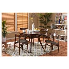 the flamingo 5 piece dining set includes a 4 ft mid century modern round dining table with curved legs and four matching chairs