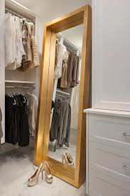a gold full length mirror sits on marble porcelain floor tiles and leans against a wall between white built in dresser and stacked clothing rails in a well