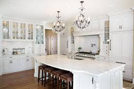 luxury kitchen with white glass face cabinets carrara marble counter island and two chandeliers