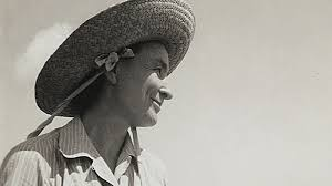 a photo of a woman in a straw hat at the ocean s edge georgia o keeffe