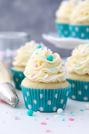 a trip of vanilla cupcakes topped with vanilla ercream the cupcakes have teal polka dot