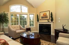 big master bedrooms couch bedroom fireplace: room  beige cream walls with white ceilings and dark brown laminate hardwood flooring dark brown round low coffee table centerpiece living room beige leather armchair cushion sofa black frame wall fireplace