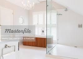 chandelier over soaking tub in modern bathroom stock photo