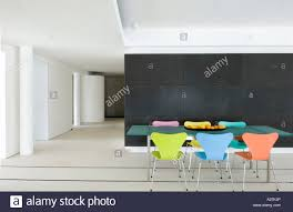 modern dining table with coloured chairs. glass dining table with coloured butterfly chairs in modern minimalist warehouse conversion e