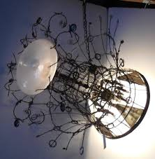 whimsical recycled materials fantasy steampunk chandelier a rocket taking off leaving a trail of light