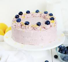 A Lemon Cake Covered With Blueberry Buttercream And Garnished With