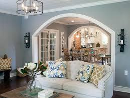 The wall dividing the living and dining rooms is opened up with a wide  archway for a more open feel. The distinctive patterned ceiling tiles were  retained ...
