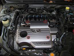 replacing spark plugs and igntion coils nissan maxima infiniti i30 next you will locate the four nuts on the plastic engine cover and remove them which are highlighted in red