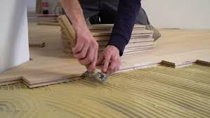 carpenter worker installing wood parquet construction in a renovated room installation of parquet