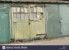 old garage door in contrast with new garage doors