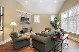 the darker wood floors contrast the light tan walls and stone fireplace the patterned rug and dark furniture offer a contrast and the