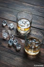 two glasses of whiskey with ice cubes served on wooden planks vintage countertop and a