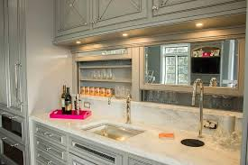 fabulous wet bar boasts gray raised panel cabinets paired with white marble countertops and a gray framed mirrored backsplash which slides open to reveal