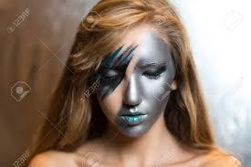 stock photo woman with silver art make up part of face blue lips portrait of beautiful young woman lady hitman techno future progress