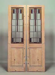 pair of stripped american mission doors inset with with geometric clear and stained glass panels