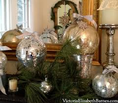 decorating a mantel with evergreen garland and mercury glass ornaments