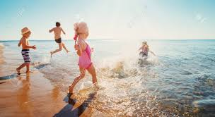 happy kids on vacations at seaside running in the water stock photo 104782539