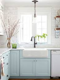 an enlarged window above the sink allows plenty of sunlight to stream into the cottage kitchen